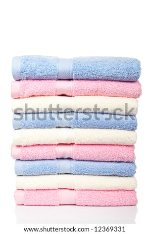 A multicolored towels stacked and reflected on white background - stock photo