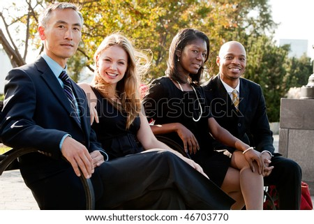 A multicultural business team on a bench in a park