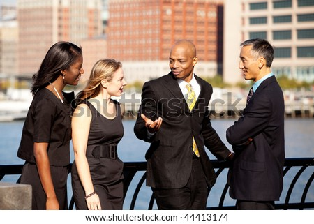A multicultural business team outside in discussion - stock photo