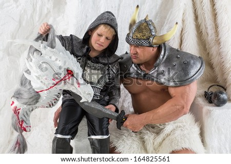 A muscular father in costume viking with a sword and young son with dragon head