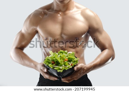 A muscular guy and fresh Salad bowl,shaped abdominal, isolated gray background - stock photo