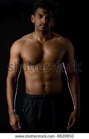A muscular Indian man on black background