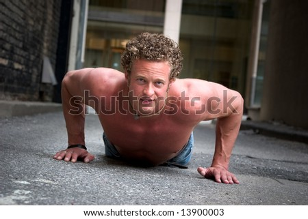A muscular man does pushups on the street - stock photo