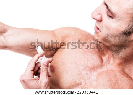 a muscular man giving himself a steroid injection in his arm - stock photo