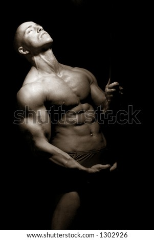 a muscular man posing artistic - stock photo