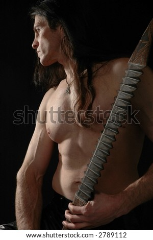 A muscular warrior with his sword drawn - stock photo