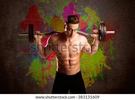 A muscular young bodybuilder lifting weight and showing his hot body with muscles in front of an urban painted wall concept - stock photo