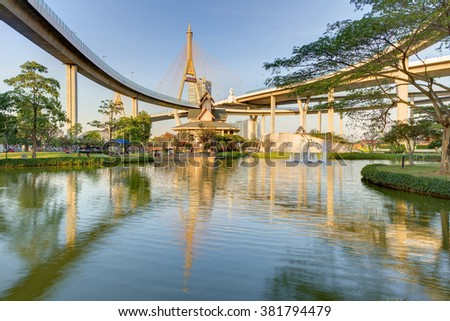 A museum by the lake in Lat Pho Park under Industrial Ring Road Bridge (or Bhumibol Bridge) in Bangkok, Thailand ~ Scenery of elevated highway interchange and bridge tower reflecting on lake water - stock photo