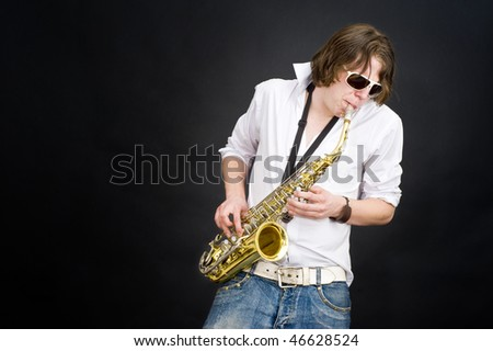 A musician in a white shirt jamming away on a saxophone, improvising - stock photo