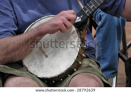 A musician sits and plays his Banjo.