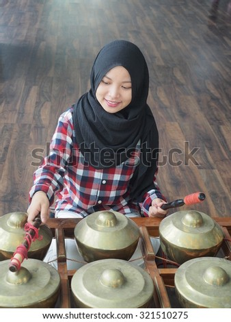 A muslim girl practicing the gamelan traditional musical instrument. - stock photo