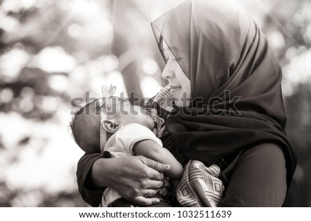 A Muslim mother from Indonesia with her baby pose together in black and white