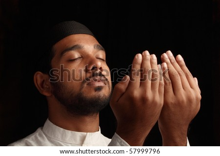 A Muslim praying in darkness - Side view - stock photo
