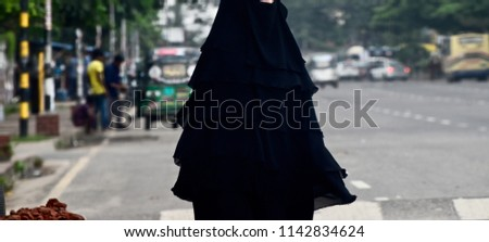 A muslim woman wearing burka with hijab walking in the road unique photo
