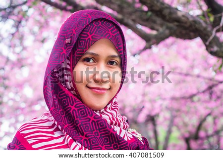 A muslim women with sakura trees as background