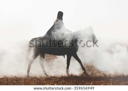 A mysterious horseman on a horse walks through the thick smoke. Girl in a raincoat on a horse in the fog - stock photo