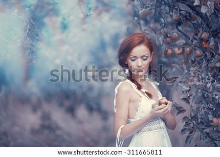 A mysterious woman in the apple garden, mysterious atmosphere - stock photo
