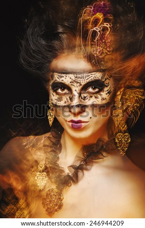 A mysterious young girl in a mask and with an unusual makeup portrait of a close-up shot using the technique of mixed light - stock photo