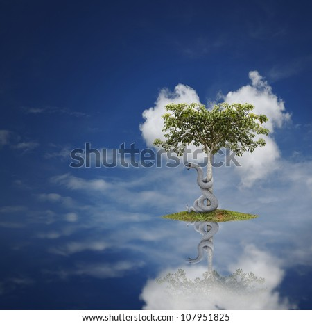 A mystical snake slithering around a tree on a tiny grass island with reflection in the water on a blue cloudy day. - stock photo
