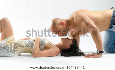 A naked man lying on the floor while a woman steps on his chest with a red stiletto - stock photo