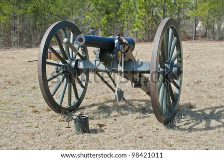 A Napoleonic style civil war cannon and cais-son in front of a confederate camp. - stock photo