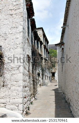 A narrow alley in a Buddhist monastery in rural Tibet. - stock photo