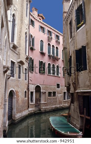 A narrow canal lined with homes in Venice. - stock photo
