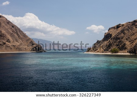 A narrow channel runs between two islands in Komodo National Park, Indonesia. This particular channel is a famous dive site called Shotgun. - stock photo