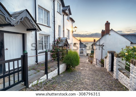 A narrow cobbled street lined with pretty cottages at Clovelly in north Devon - stock photo
