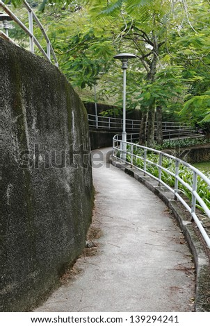 A narrow concrete path through a green park.  - stock photo