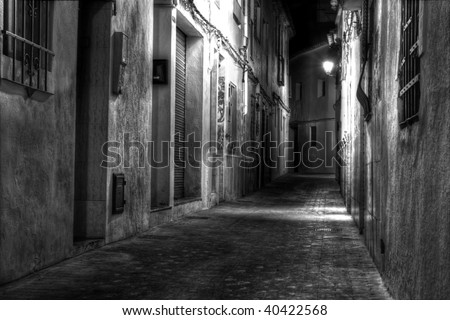 A Narrow European Street at Night in Black and White - stock photo