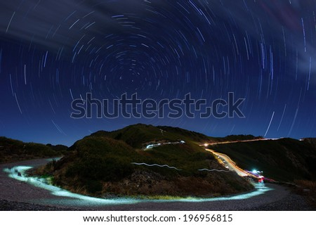 A narrow road winds up a hill under a starry sky. - stock photo