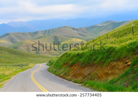 A narrow secondary road winds its way into the Southern Sierra Nevada Range in California back country, where a storm awaits. - stock photo