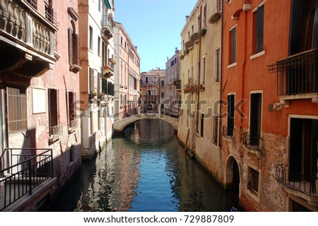 a narrow street in Venice crossed by water