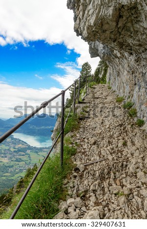 A narrow trail hiker, lake of Annecy in the background - stock photo