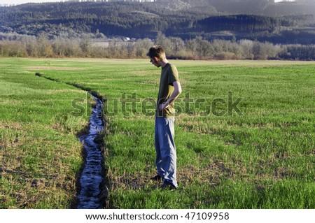 A narrow water river stream going through a green grass field landscape. - stock photo