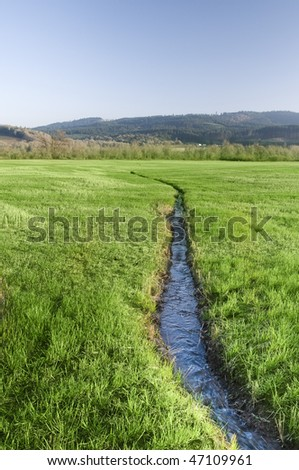 A narrow water river stream going through a green grass field landscape.