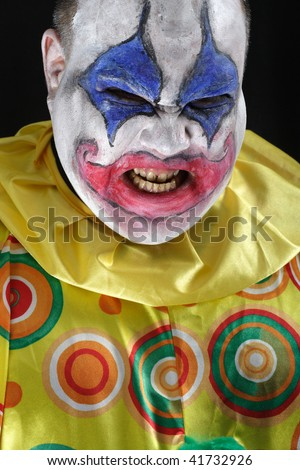 A nasty evil clown, angry and looking mean. Harsh lighting from below, focus on the teeth.