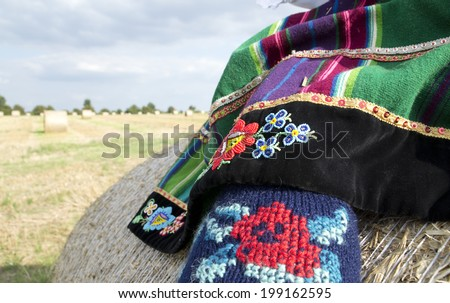 A national and traditional Polish skirt and leggings with a folk emblem in the field of harvest straw bales
