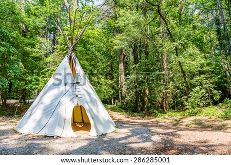 A Native American teepee in a wooded clearing - stock photo