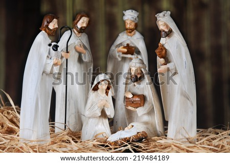 A nativity scene composed of Mary, 3 wise men, 2 Shepards and baby Jesus.  All on a floor of straw in an old wood barn.  Shallow depth of field with focus on Mary. - stock photo