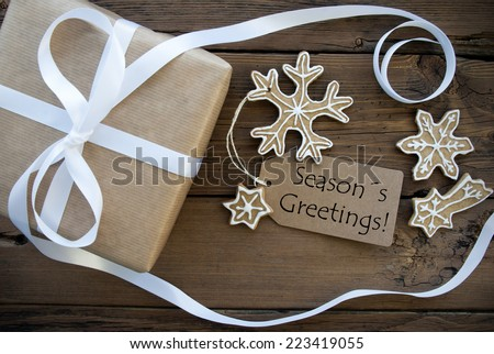 A Natural Looking Gift with white Decorated Ginger Bread Cookies and a brown Label with Season's Greetings on it - stock photo