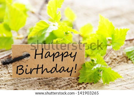 a natural looking label with happy birthday and green leaves and wood as background - stock photo
