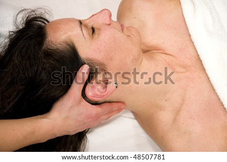a natural mature woman having a massage at her neck muscles