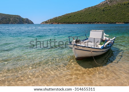 A natural port with a fishing boat anchored by the beach - stock photo