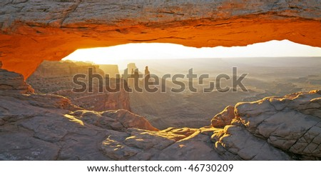 A natural sandstone arch, glowing orange with the sunrise, in Canyonlands National Park, Utah. - stock photo