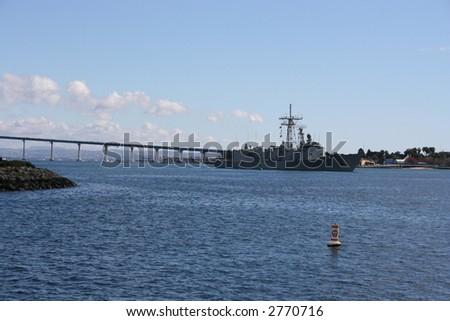 A Navy Battle ship in San Diego Harbour.  Coronado Bridge in the background. - stock photo