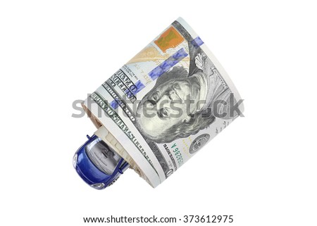 A navy blue metal car inside a roll of American Dollar banknote money isolated on white - stock photo