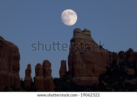 a nearly full moon rises over red rock spires near Sedona, Arizona - stock photo