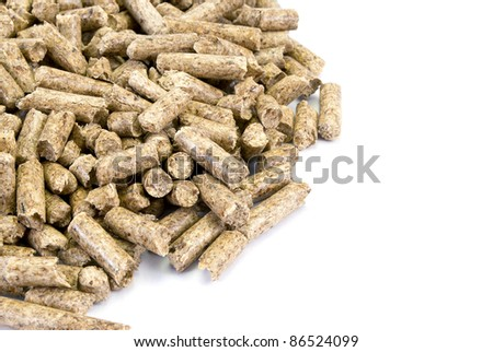 A neat pile of wood pellets, isolated on white. Fragment. - stock photo